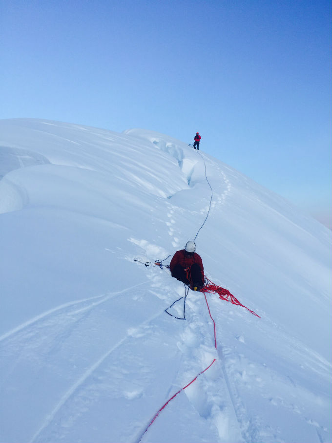 Two roped climbers approach the snowy summit of Mount Huntington