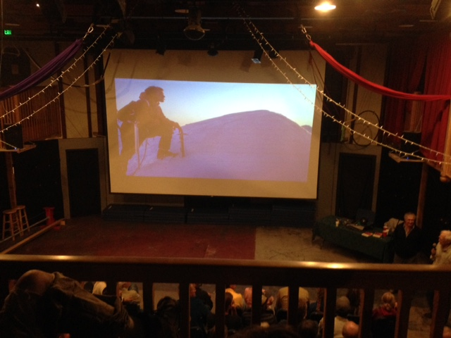 Theater screen depicting a slide of climber near the summit of Mount Huntington