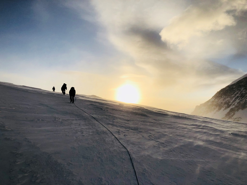 A rope team climbs a snowy ridge during sunset