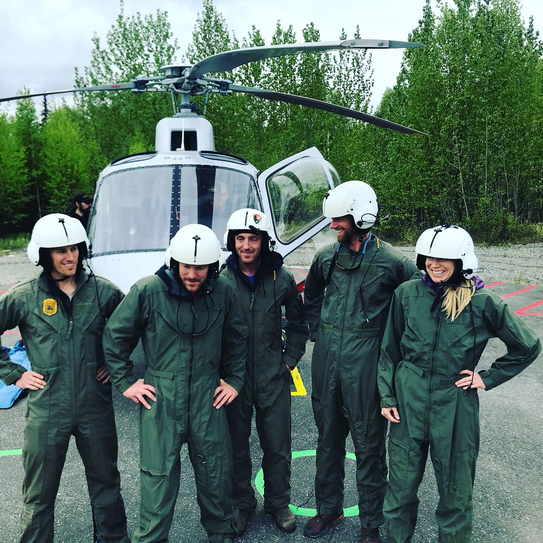 Five volunteers in flight suits take a break during helicopter training