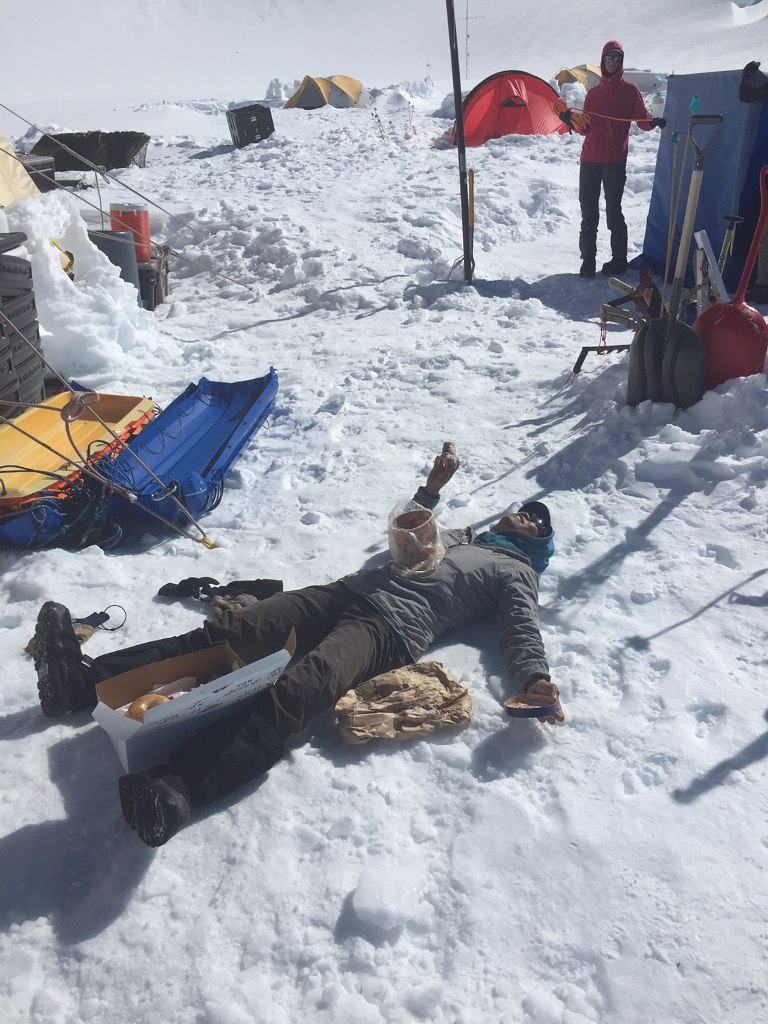 Mountaineer lies flat in the snow with a box of donuts and tub of ice cream on her chest