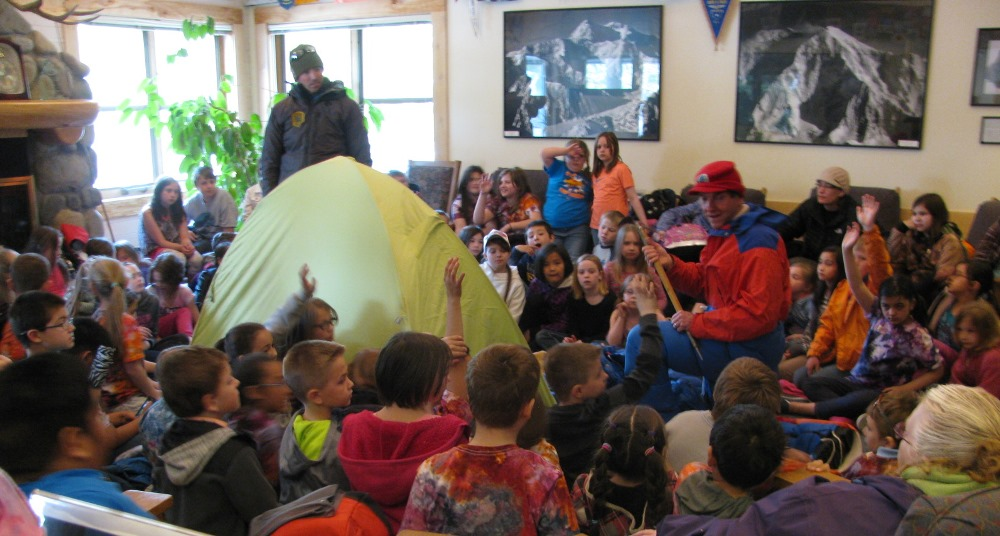 Students surround a tent and two climbers at the Talkeetna Ranger Station