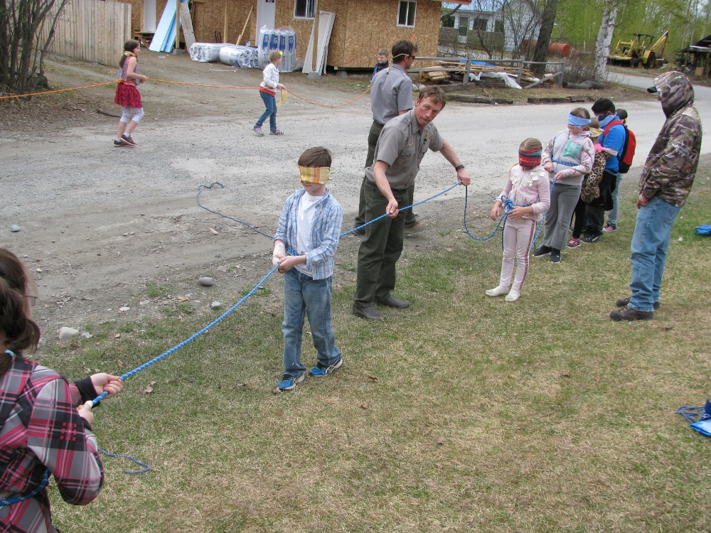 Blindfolded kids walk on a rope line