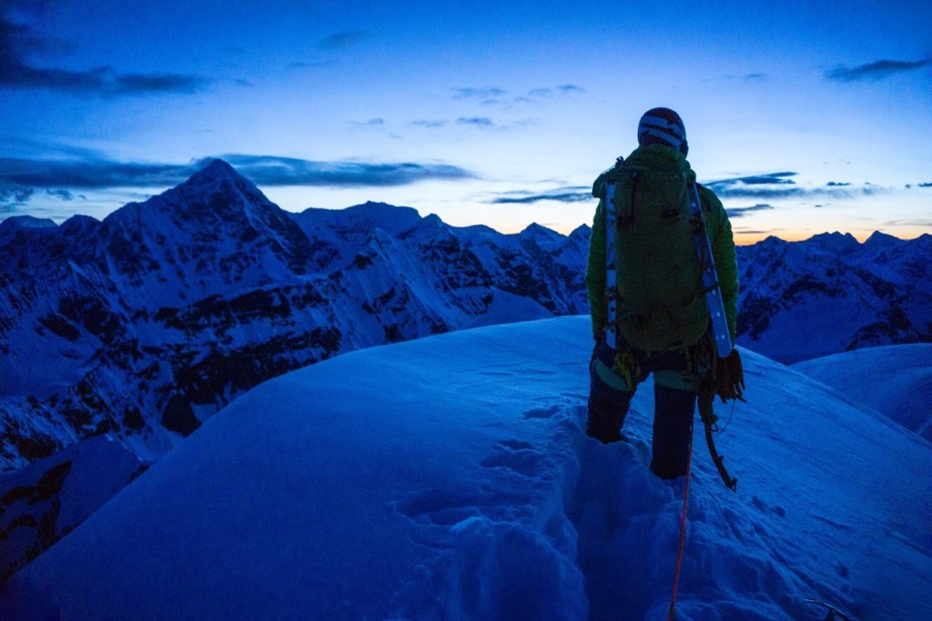 A climber on top of a snowy peak stares off into a distant sunset