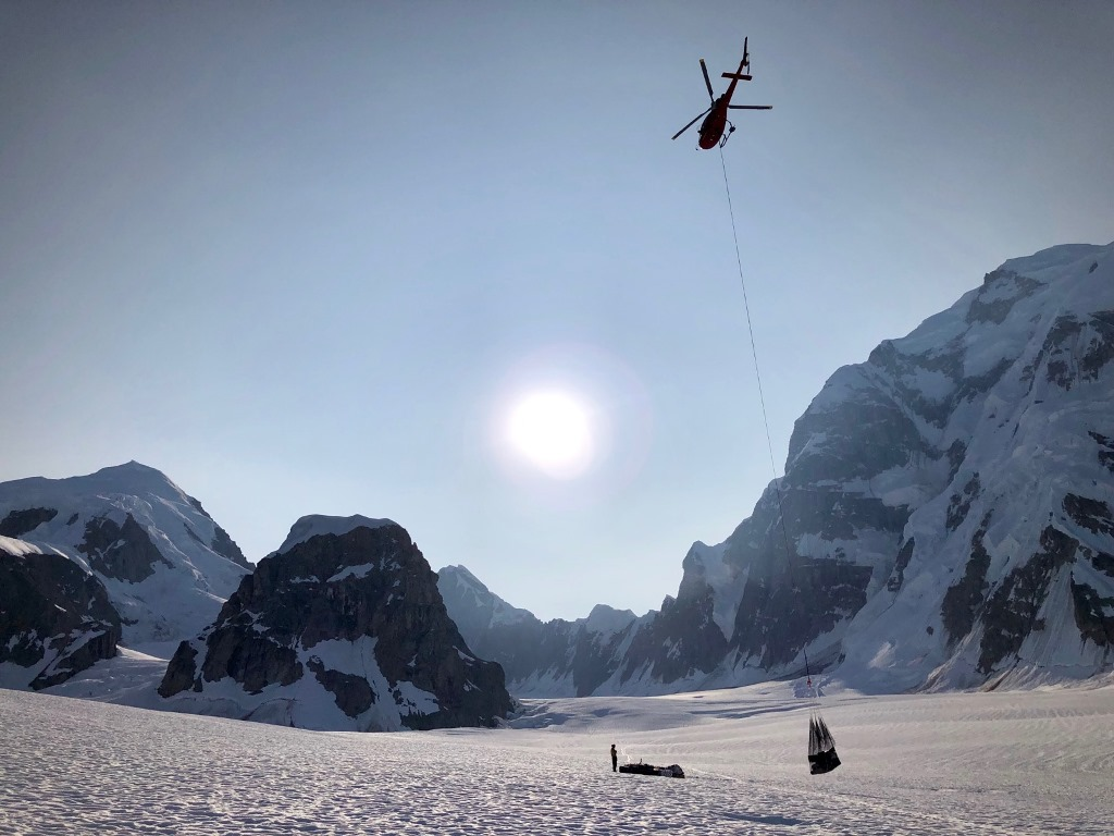 A helicopter hovers over a netload of gear suspended by a rope