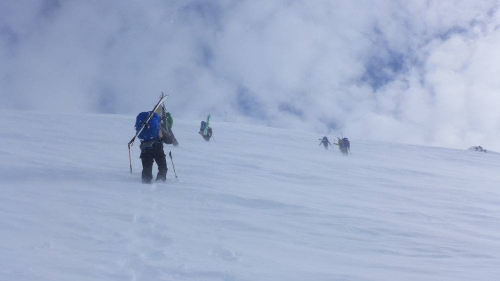 Four climbers ascend a slope in blowing snow