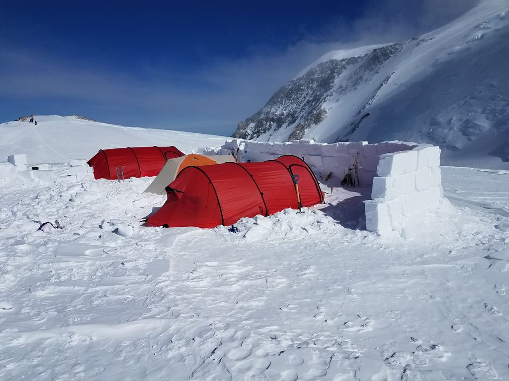 Three tents on a glacier shielded on one side by a snow wall