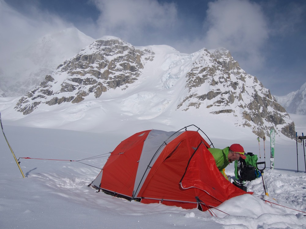 Ranger emerging from tent on a glacier