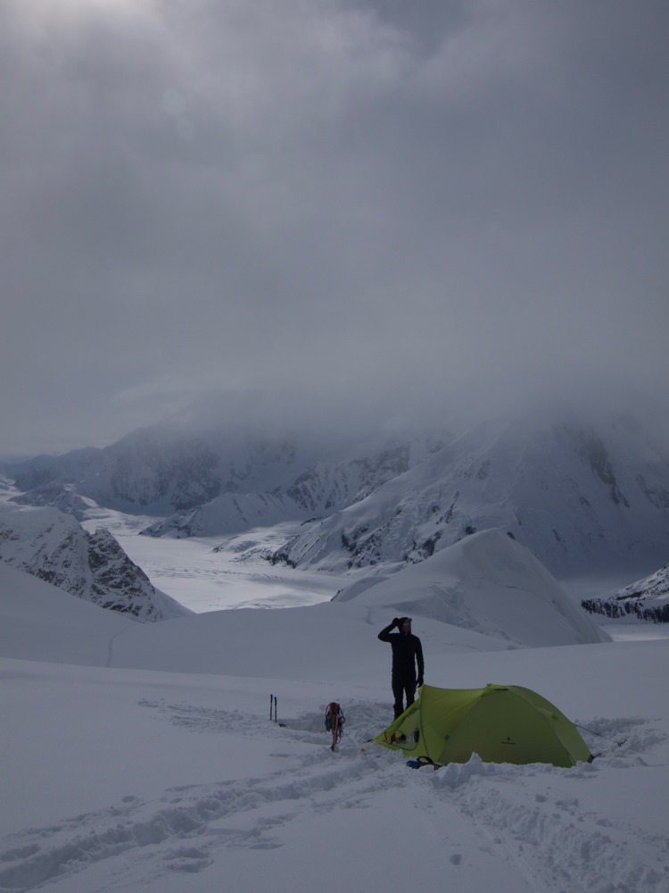 Ranger standing outside a tent with peaks and glaciers in the background