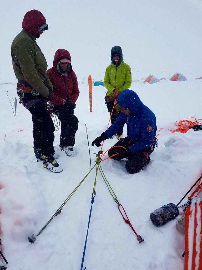 A ranger kneels in the snow explaining a rope rigging system to fellow rescuers