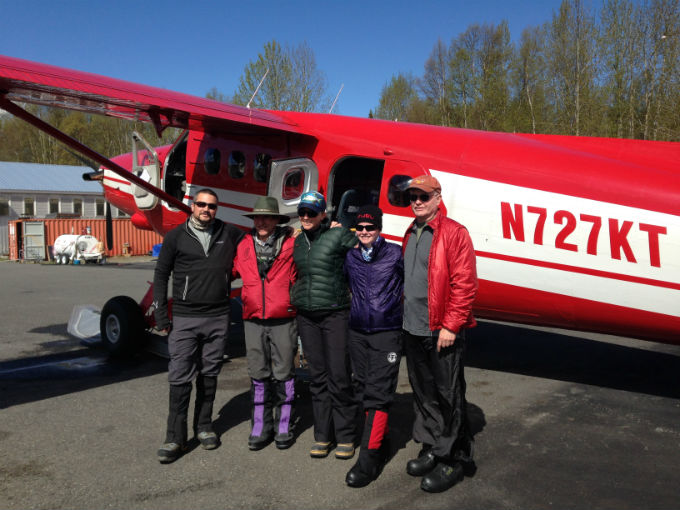 Five climbers pose for a photo outside a small airplane