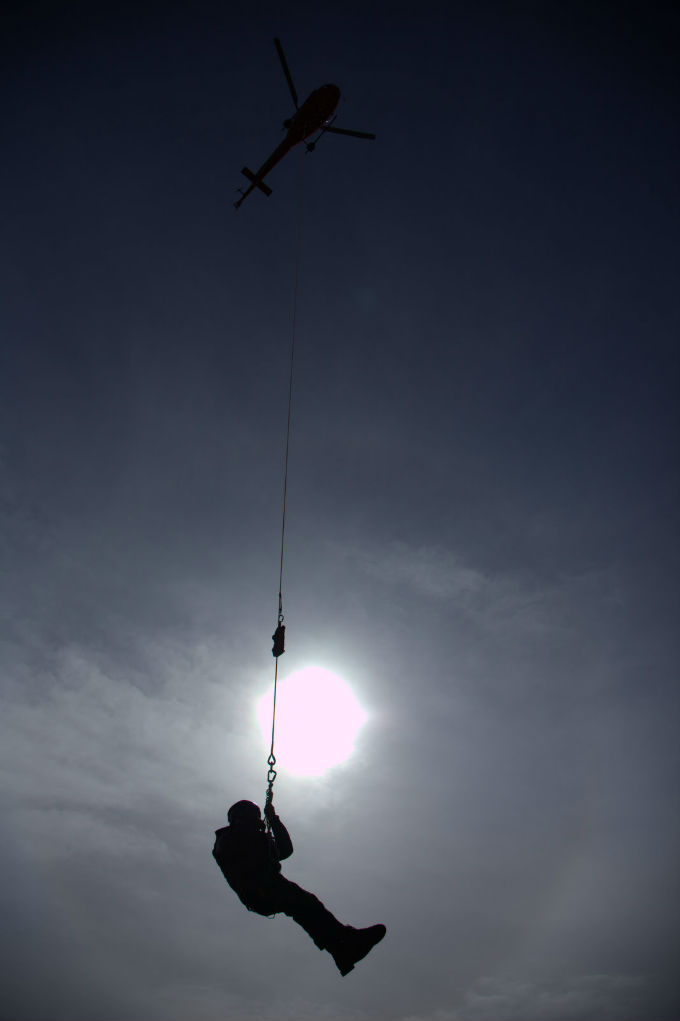 A ranger hangs from a short-haul line under a helicopter.