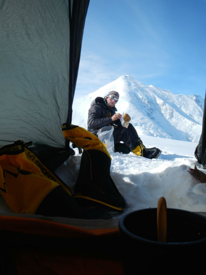Looking out a tent to a snacking climber seated in the snow