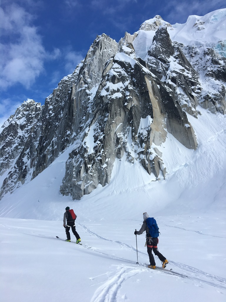 Two rangers ski tour below the rock face known as the Crown Jewel