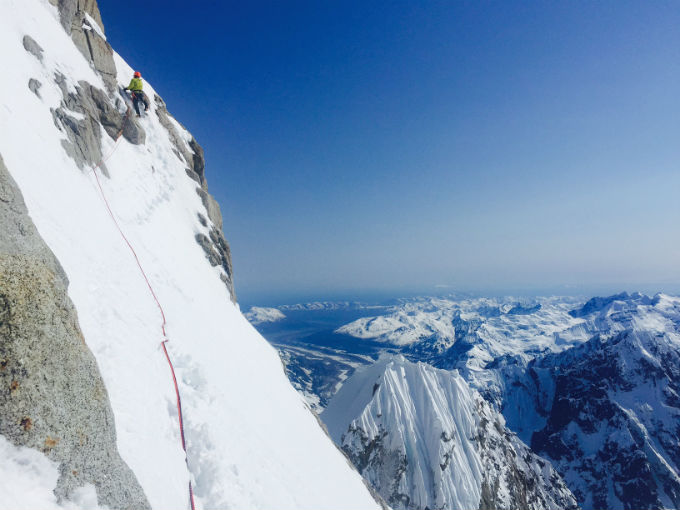 A roped climber ascends a steep rock and snow face with dramatic views of the Alaska Range in the distance