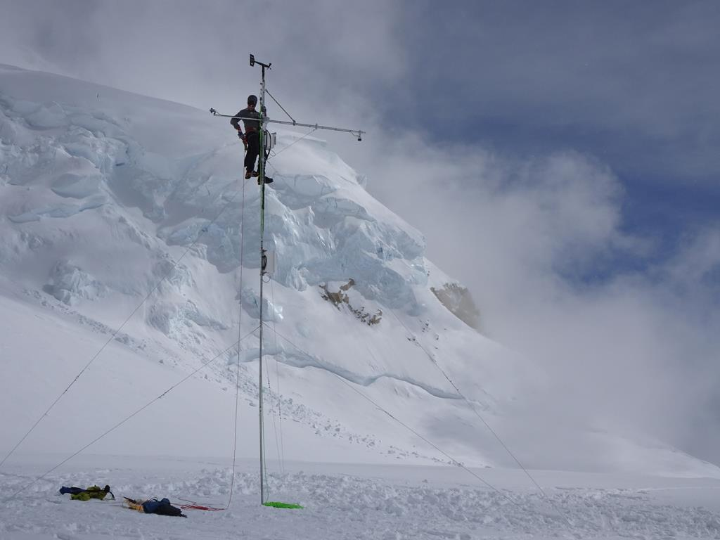 A park ranger climbs a tall metal pole to install weather equipment