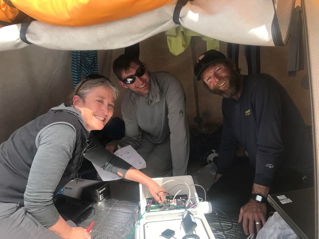 Three scientists troubleshoot the weather station equipment in a tent at Basecamp
