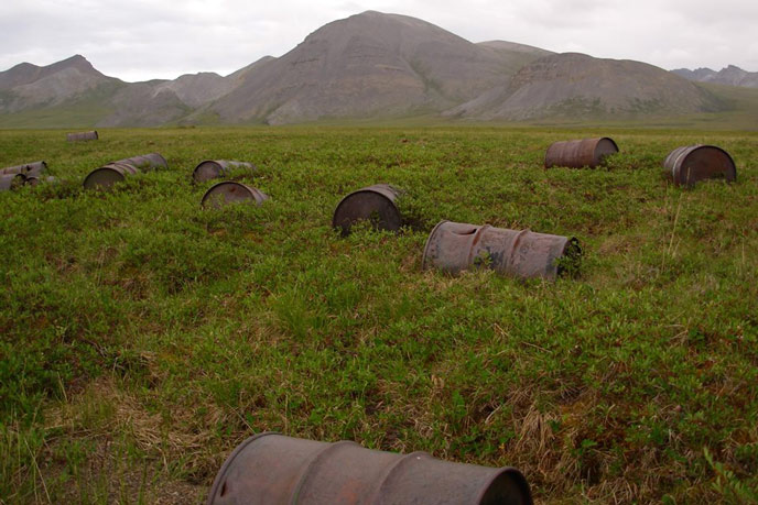 rusty barrels in a tree-less field, mountains in the distance
