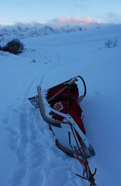 snowy landscape and a sled turned on its side
