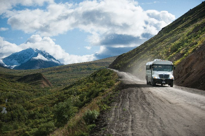 A white bus travels along a gravel road