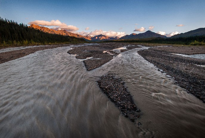 View above a braided river with snow-capped Alaska Range in distance
