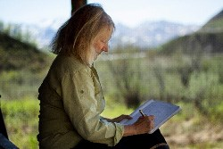 Author Kathleen Dean Moore writes on the porch of the East Fork Cabin