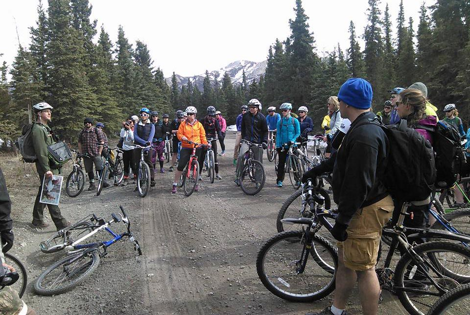 a ranger standing among a large group of bicyclists on a dirt road