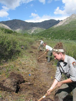 Female park ranger in foreground, male volunteer in background digging along trail edge, mountain in background