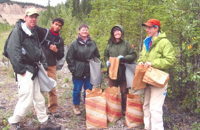 five people standing in the backcountry holding paper bags