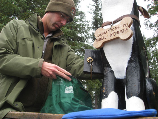 "ranger pulling cash out of a wooden dog that bears a sign reading ""donations to the denali sled dog kennels"""