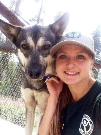 Youth Conservation Corps volunteer poses with sled dog