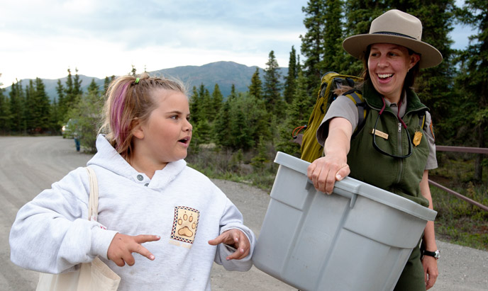 Park ranger walks and listens to a young girl