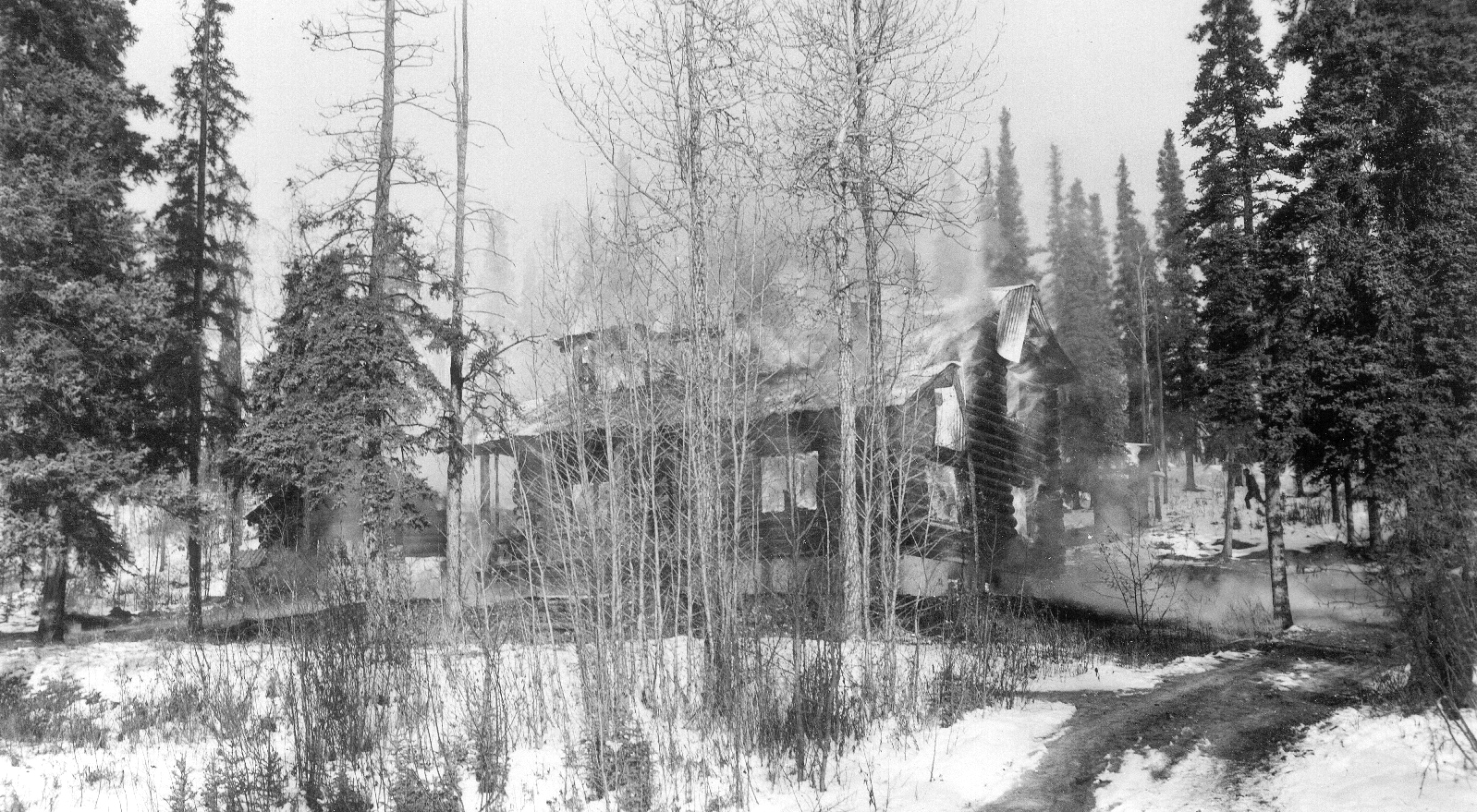 black and white image of a partially burnt building in a snowy forest