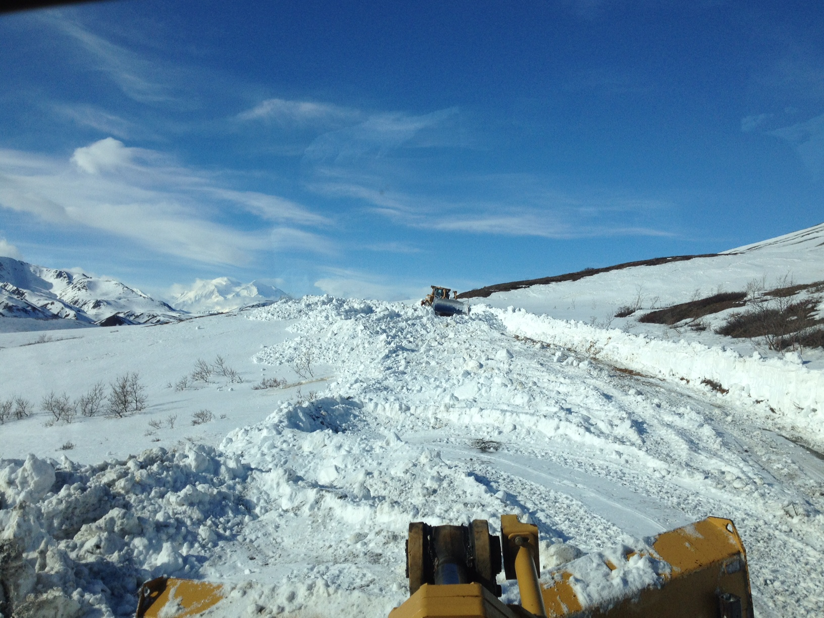 two large machines plow a snowy road on a hillside under a beautiful blue sky