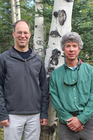 two men posing for a photo in front of aspen trees