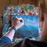 Woman painting landscape on small canvas