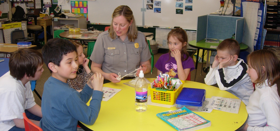 a ranger helps students with a craft