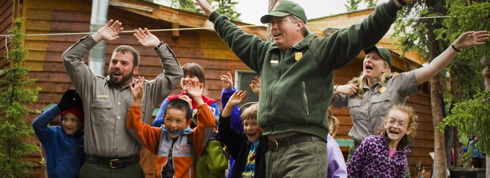 a group of students and rangers practice waving their arms in case of a bear encounter