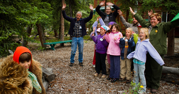 "Children and ranger with hands in the air, practicing ""hey bear!"" etiquette"