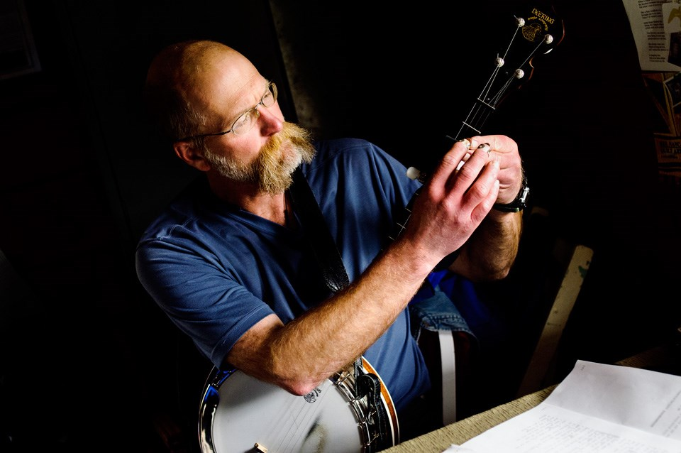 Musician places a capo on the neck of a banjo