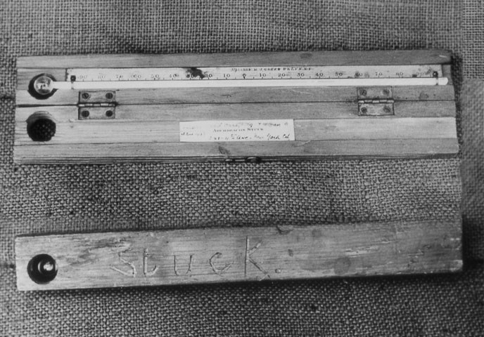 "A historic black and white photograph of a wooden thermometer with the name ""Stuck"" carved into it."