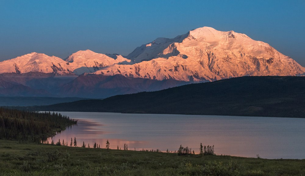 A Vast White Mountain Looming Over Smaller Mountains And A Landscape Of Hills And Lake