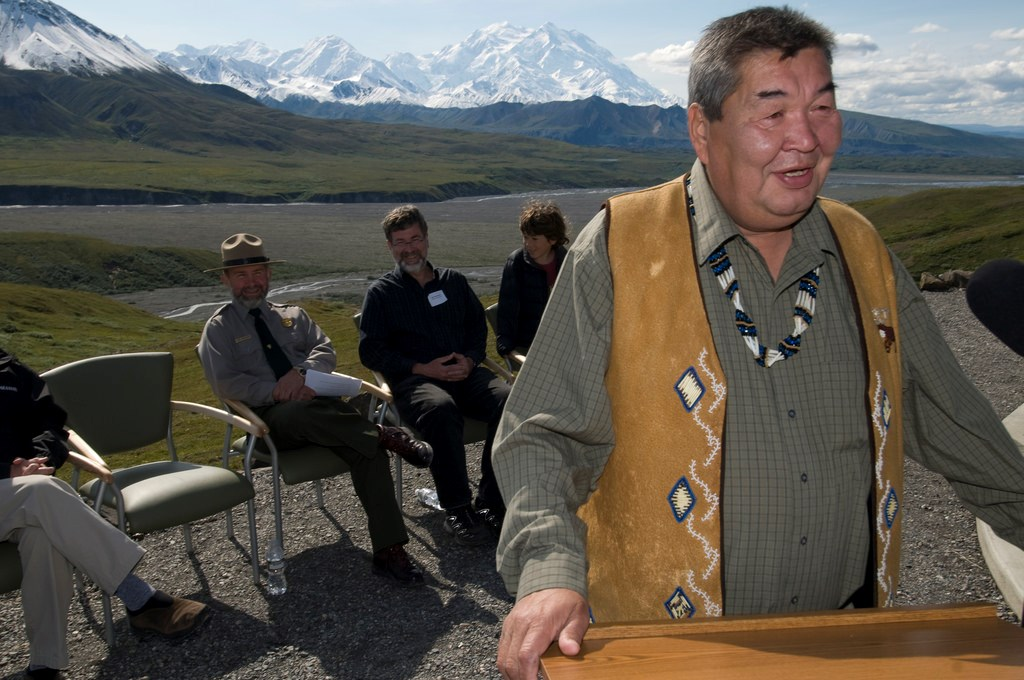 an alaska native man speaking at a lectern outside in front of several seated people. denali, a vast snowy mountain, is in the distance