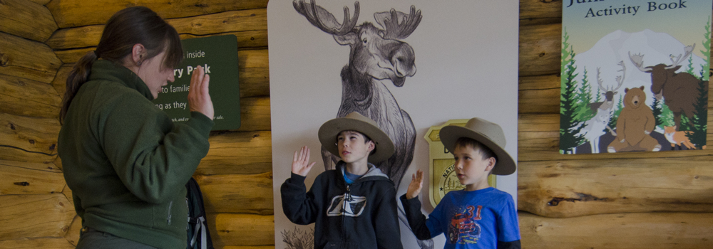 two junior rangers are sworn in by a park ranger