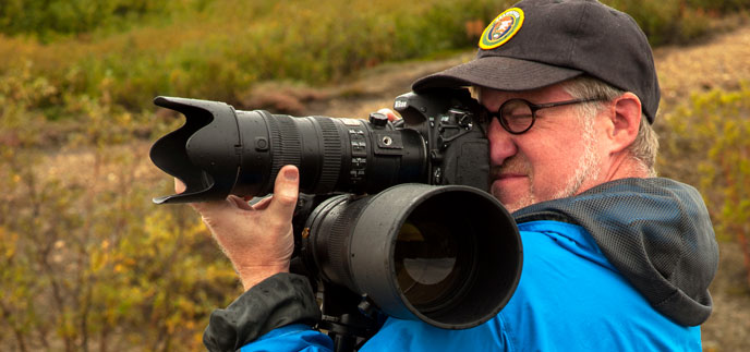 Volunteer photographer Kent Miller holds two DSLR cameras with long lenses