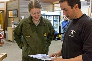 uniformed ranger and firefighter in black t shirt look at a map together