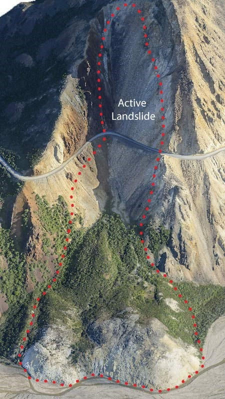 "aerial view of a mountainside with a large circled area, one high up labelled ""active landslide"" running from near the peak of the mountain, down past a road on the mountainside, to the foot of the mountain"
