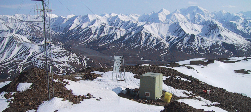 an earthquake station sits on a snowy mountainside