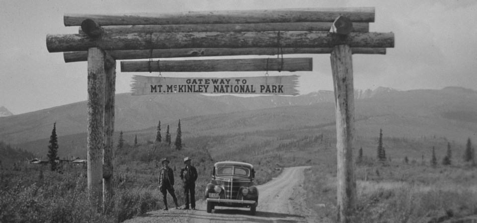 two people stand next to a car on a dirt road under a sign for Mt. McKinley National Park