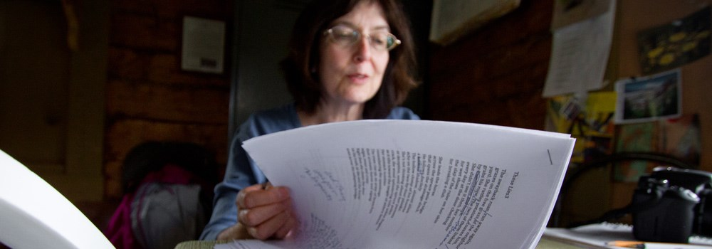 a woman sorts through a stack of papers on a desk